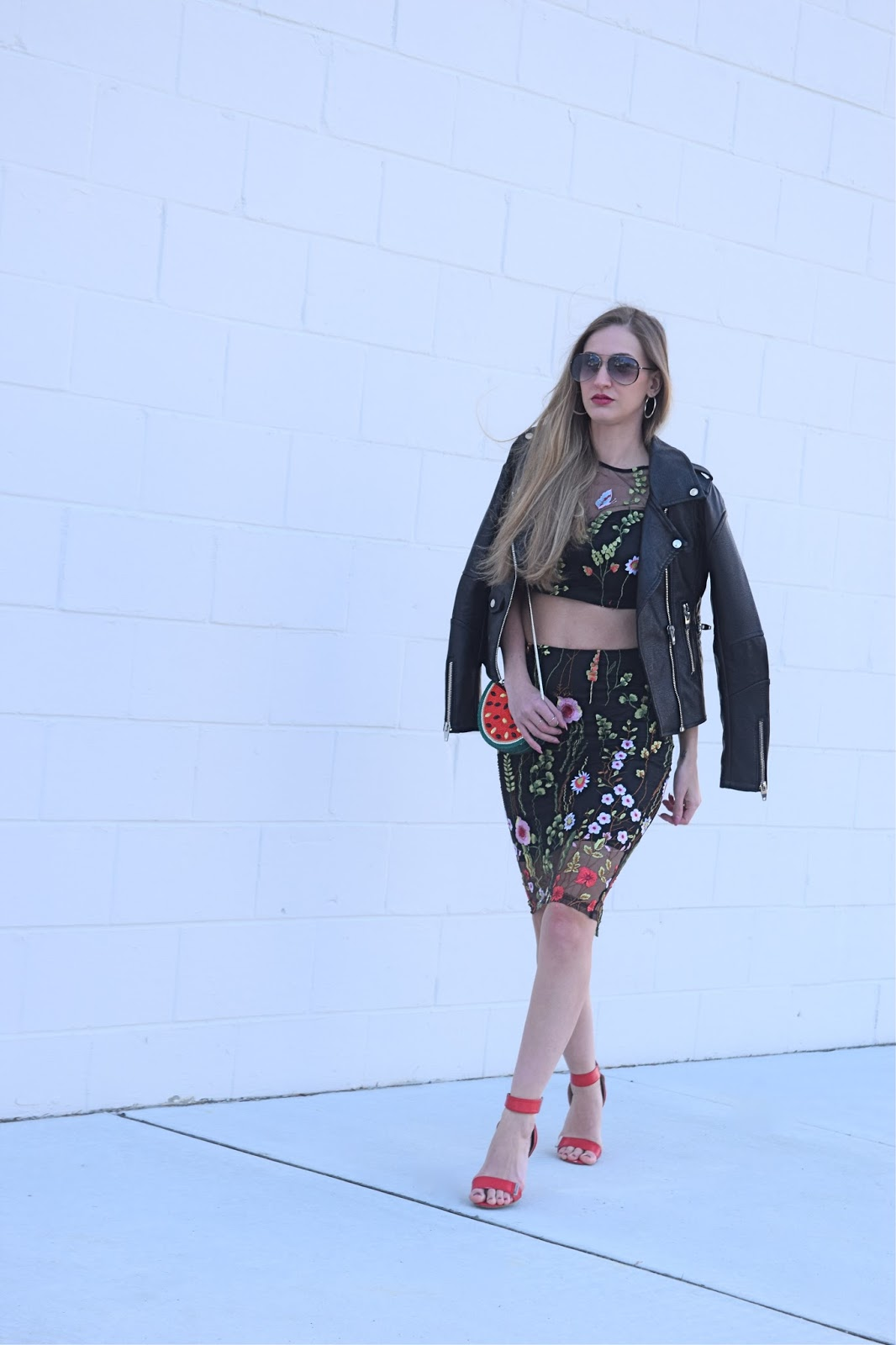 Wearing Shein Black Botanical Embroidered Mesh overlay crop top with pencil skirt, natasha couture crystal watermelon clutch, wearing steve madden red ankle strap heels, blank nyc black leather jacket spring wedding two piece outfit