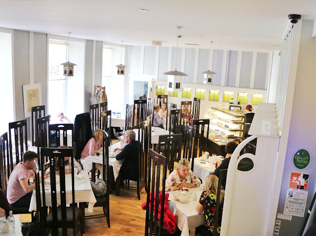 An overview of The Willow Tea Rooms in Glasgow, there are multiple tables spread out and every seat is taken up