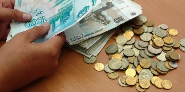 Гора монет и веер купюр