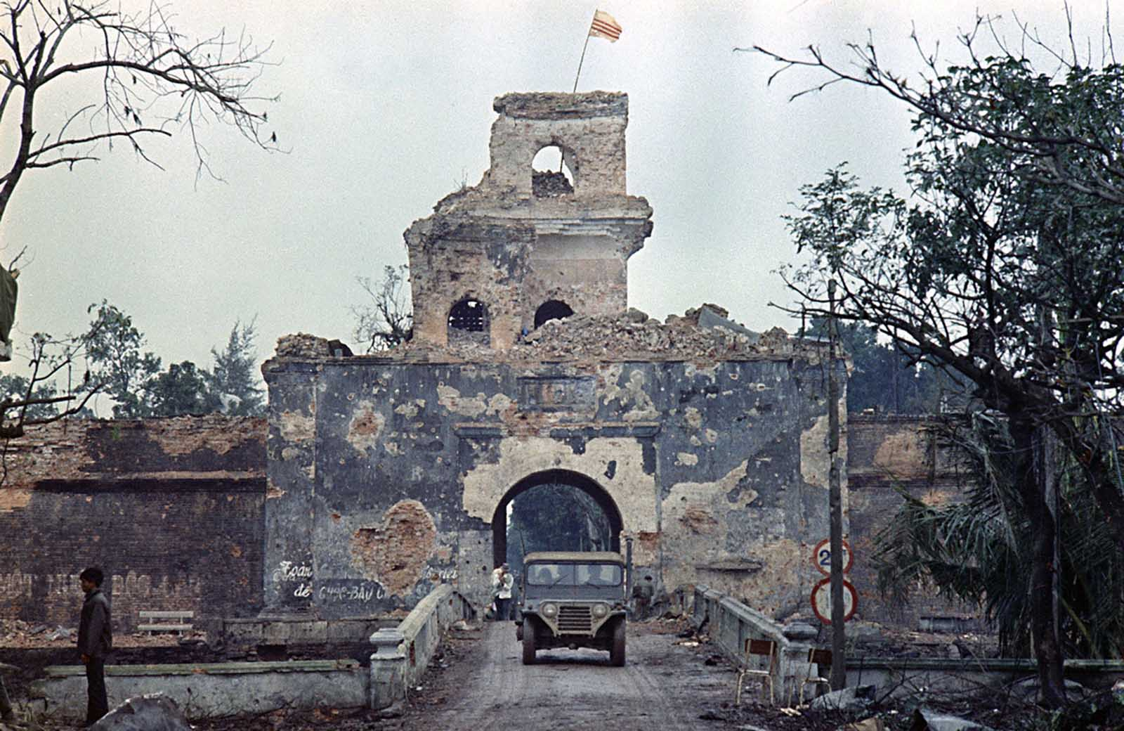 The flag of the Republic of Vietnam flies atop a tower of the main fortified structure in the old citadel as a jeep crosses a bridge over a moat in Hue during the Tet Offensive, February 1968.