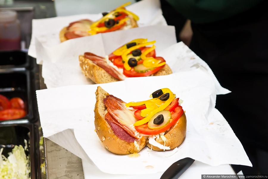 Приготовление сэндвича. Добавляются оливки, сладкий перец