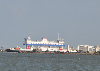 blue and white ferry boat at the Bolivar Peninsula dock