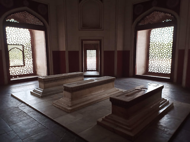Three marble tombs inside one of the sections of the Humayun's tomb building, with latticed windows behind letting light in