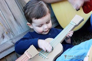 Un bebe tocando  una guitarra de cartón con cuerdas azules.