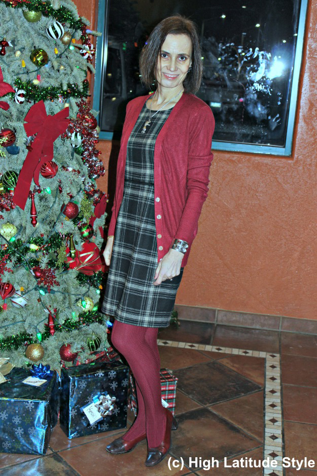 image showing a middle aged woman in a plaid dress and red tights next to a Christmas tree