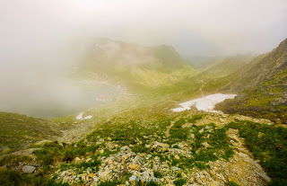 Steep slope on rocky hillside over balea lake in fog. mystic weather in romanian mountains