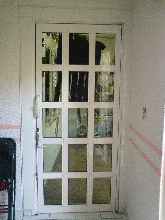 puerta abatible en aluminio blanco lacado linea de pulgadas con total de duela de cinco ondas y pasador como seguro en ambos lados