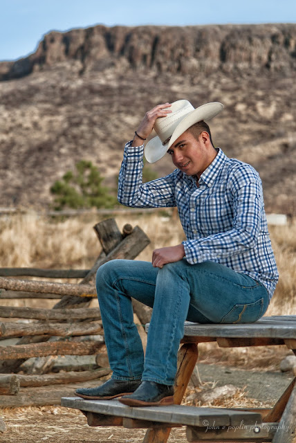 a high school senior sits on a rustic picnic table in Colorado for his senior portraits