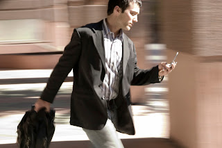 Businessman looking at phone on the go