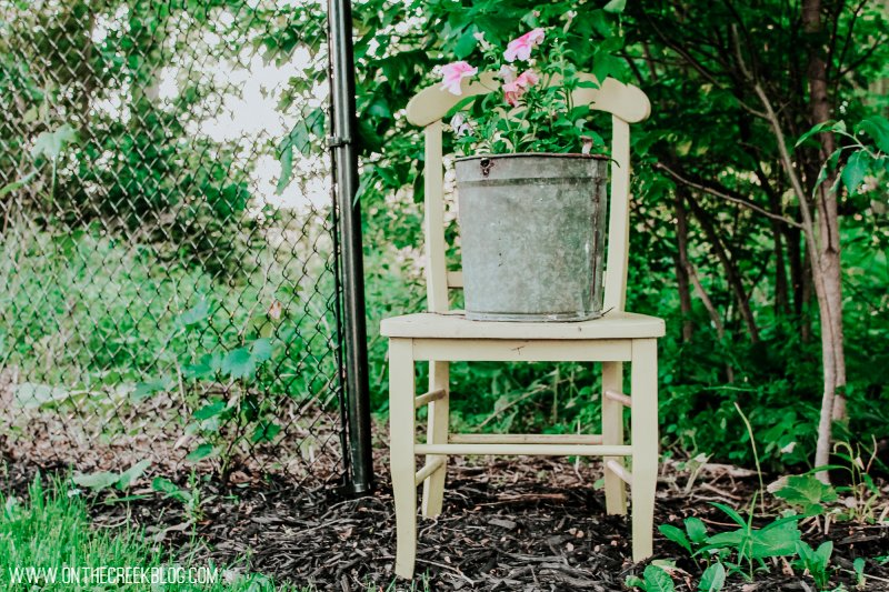 Flower chair planter idea.  Yellow chair with sap bucket on top!