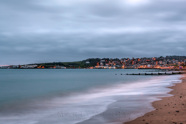 Swanage seafront lit up in the early morning under a cloudy sky