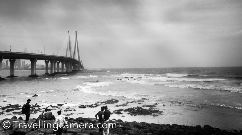 While in Mumbai , we visited Bandstand that was a little disappointing experience for me and if you are wondering why, check this .  After roaming around Bandstand, we walked towards Taj Lands End and finally reached Castella De Aguada towards the end. It's just across the sea and Sea-Link looks awesome from this place. This Photo Journey shares more about Castella De Aguada and why it's so popular amongst locals and tourists visiting Mumbai.It's also called at Bandra Fort. The Portuguese had established a base in this area during 1530s after defeating Bahadur Shah of Gujarat state of India. And they built various sea-forts along the western Indian coastline. Castella de Aguada  was one such strategically located fort, overlooking the Mahim Bay to the south, the Arabian Sea to the west, the islands of Worli to the south and the town of Mahim to the south west.During the Portuguese rule, it was armed with seven cannons and other smaller guns as defense.  Here is huge wall of Castella De Aguada from where you can enjoy awesome views of Sea Link and get photographs clicked. And in monsoons the views are even better with clouds in sky and everything cleaned up by drizzles.Above photograph shows the open space just in front of the fort and if you would try to search the fort, you would be disappointed. There is hardly anything which remained and look like a fort. There are high walls from where you can see Sea-Link and observe sea waves. You can find vendors roaming around to sell snacks. Structure of Castella De Aguada has been renovated a decade back and now it doesn't look like old forts but some of the walls still look strong and have old charm. Are you wondering what is the significance of Castella De Aguada?Bandra Fort Garden is very well maintained. Not sure if it seemed like that because of freshness of Monsoons or it's really handled well by authorities.Lot of folks come here, spend some quality time with friends by looking at the waves. Some of them just cross the wall and sit on rocks around the wall. Just notice folks sitting on the rocks in photograph below.Quick facts . How to Reach Castella De Aguada - It's at walking distance from Shah Rukh Khan's house :). So if you are visiting Bandstand, just walk from there towards Taj Lands End and cross that. Castella De Aguada Timings - I didn't find a way to close this but it seems castle is open from 6:30am to 7pm. There must be some entry gate which I missed.