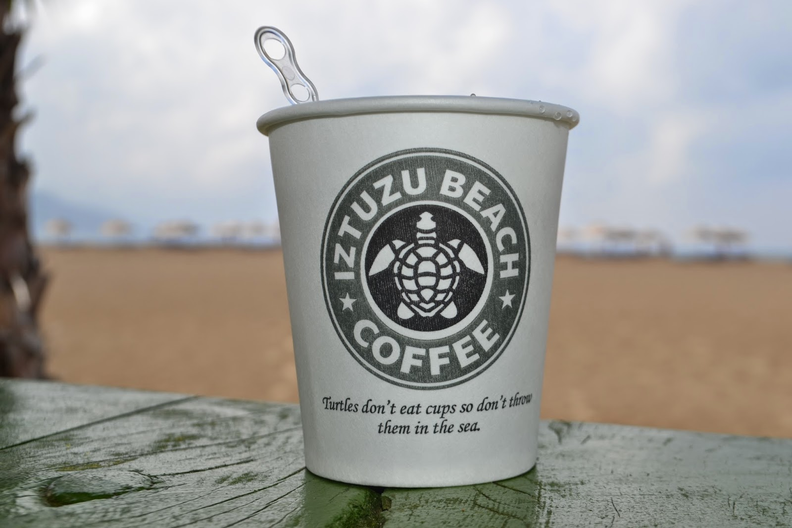 a coffee cup with the Iztuzu beach logo on the side which mimics the starbucks logo