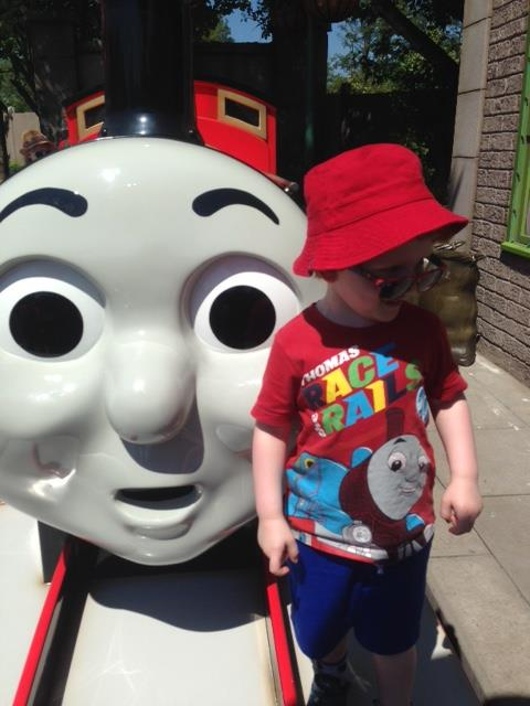Little boy standing in front of James the tank engine