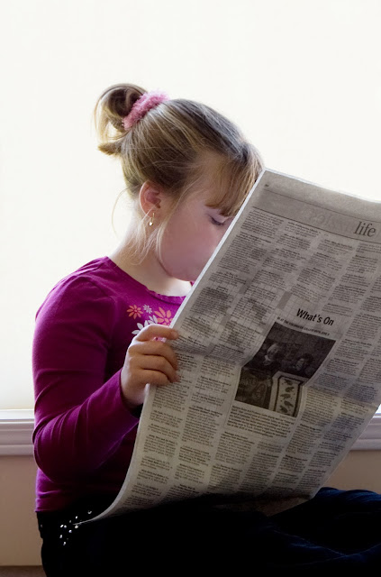 A youg girl reading a newspaper.
