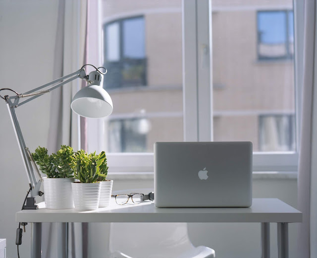 Small table in front of a window, with a laptop, a lamp and a selection of plants on it