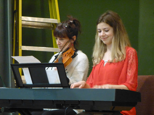 A mother-daughter fiddler and pianist playing music.