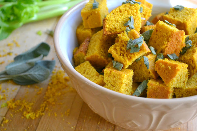 Cubed pumpkin cornbread and sage in a bowl.