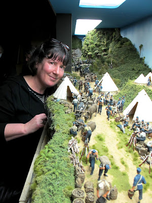 Woman standing next to a diorama of 19th-century soldiers in an encampment in the bush.