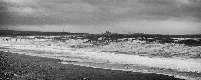 Photo of massive waves breaking on the shore with Iggesund Paperboard's Workington Mill in the distance