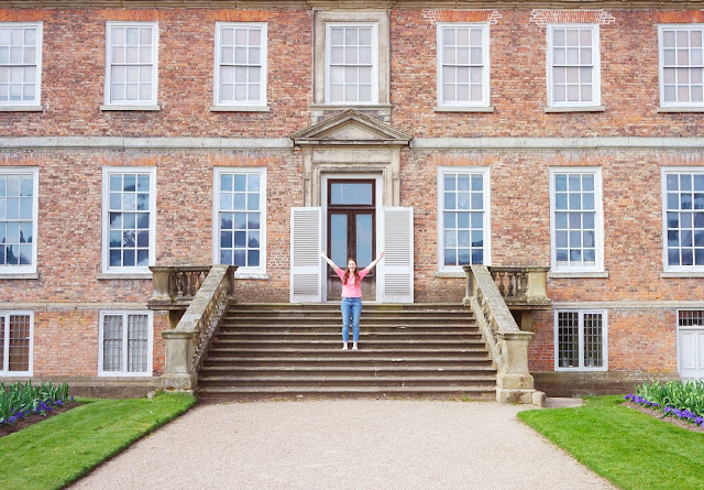 I'm wearing a pink jumper and jeans and standing on the stone steps of Erddig Hall, a red handmade brick country house with lots of windows