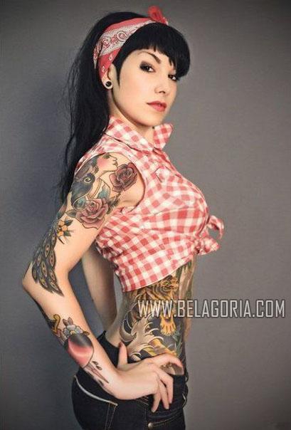 mujer de estilo rockabilly, con las manos en jarras, nos mira seductora, lleva tatuajes dold school