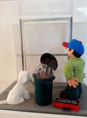 Miniature clay figure and dog, looking at a window space in a gallery exhibition.