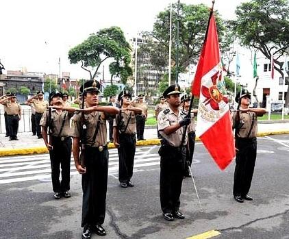 Foto de policias saludando a la bandera peruana