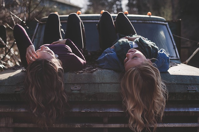 Girls Laying on Hood of Truck Upside Down