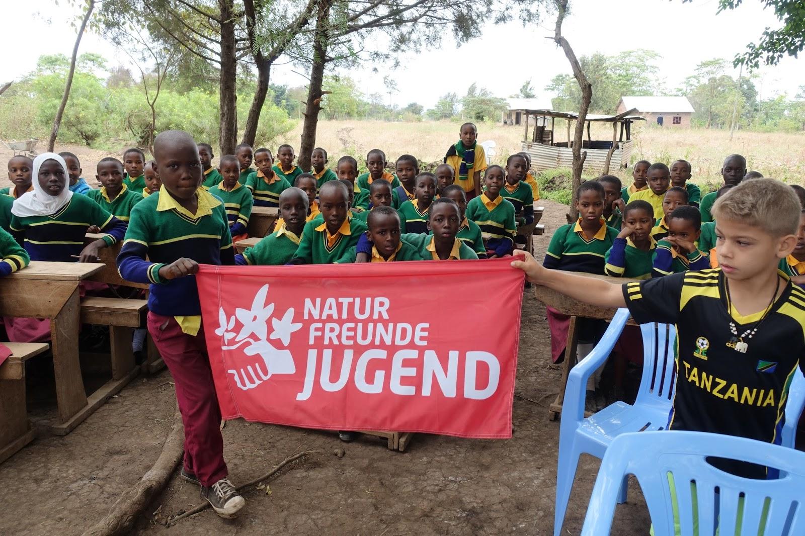 Schüler_innen mit einer Fahne der Naturfreundejugend