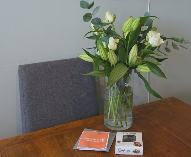 kitchen table displaying a vase of flowers, box of chocolates and notecard