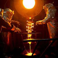 Isıya dayanıklı kıyafetler giyerek bir fırın önünde erimiş sıvı metal ile döküm yapan işçiler
