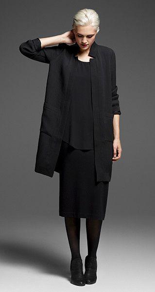 Девушка в черной юбке миди и черном длинном кардигане