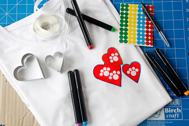 Paw print hearts made with colourful fabric markers on a white t-shirt