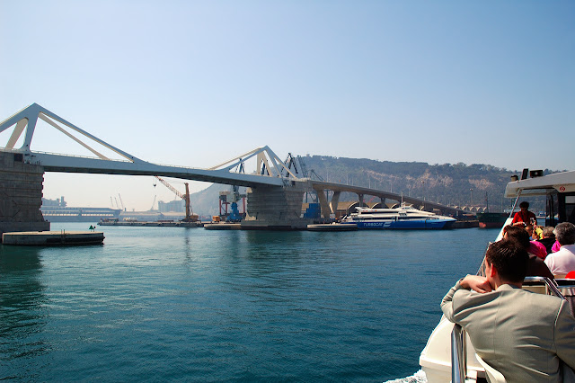 Porta de Europa Bridge as seen from sightseeing boat in Barcelona harbor