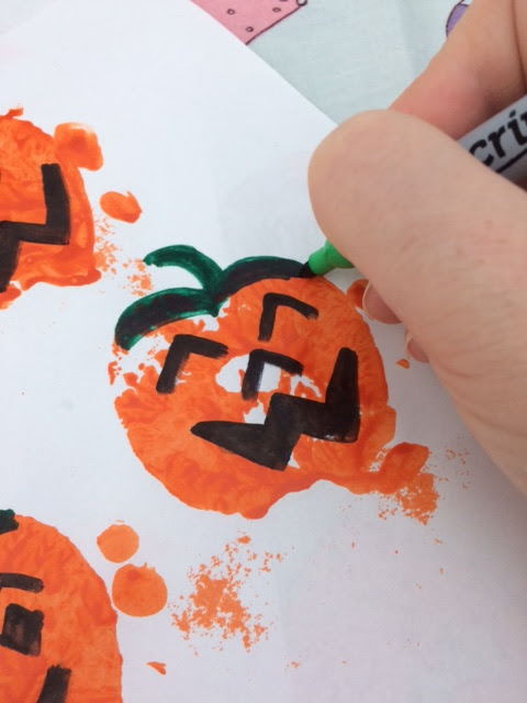 Pumpkin print made with half an apple with a face and stork being drawn on