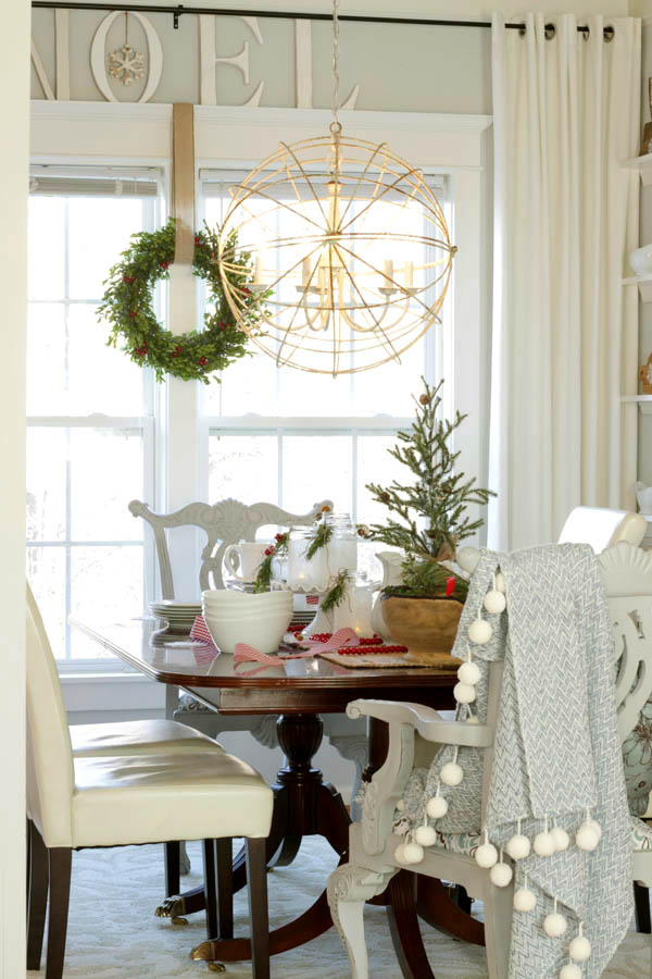 Christmas tablescape with pom pom blanket on parson chairs, and boxwood wreath on window with Noel sign