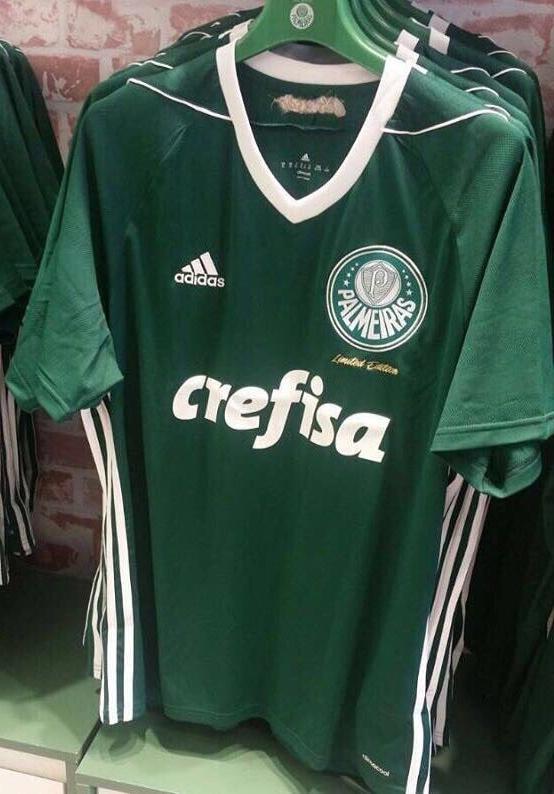 A camisa é predominantemente verde com a gola e as listras laterais em  branco. Abaixo do escudo 609782c427695