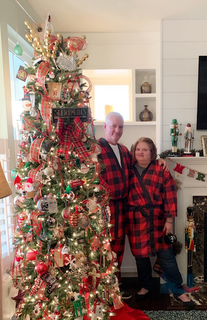 Living room decorated for Christmas with a Christmas tree, a couple wearing matching pajamas