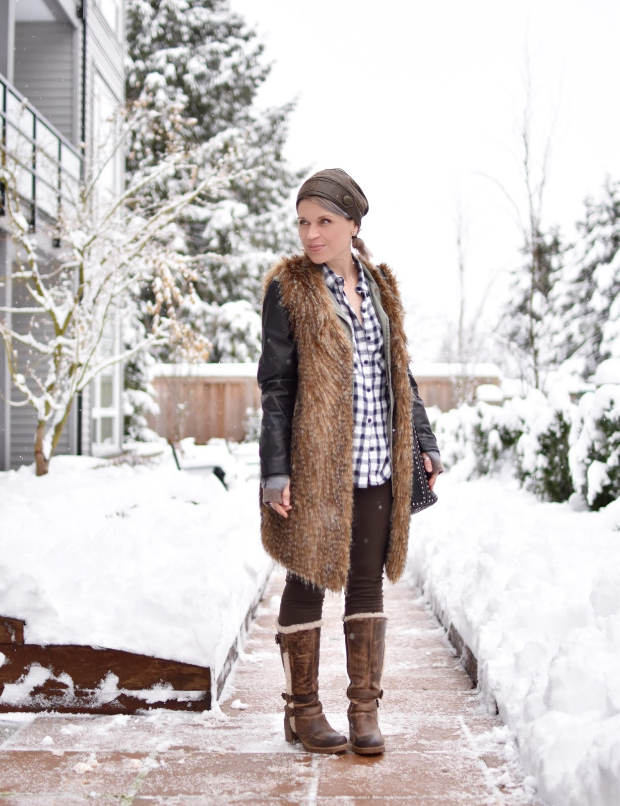 Monika Faulkner outfit inspiration - styling a military parka with a plaid shirt, long faux-fur vest, leggings, fleece-trimmed boots, and leather beanie