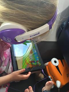 Young girl on iPad on an aeroplane