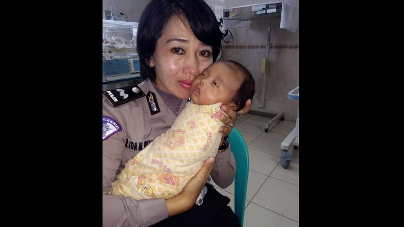 Polwan menggendong bayi yang gagal diadopsinya