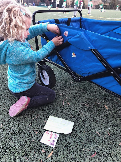 girl putting stickers on a wagon
