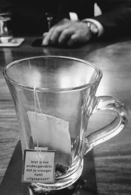 Zwart-wit foto van een glas op tafel met label van theezakje met de tekst: Wat is het ondeugendste dat je vroeger hebt uitgespookt. Tegenover zit een heer in het zwart met een glas rode wijn en een glas water.