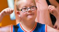 Vrolijke overwinnaarsblik van een jongetje met down-syndroom
