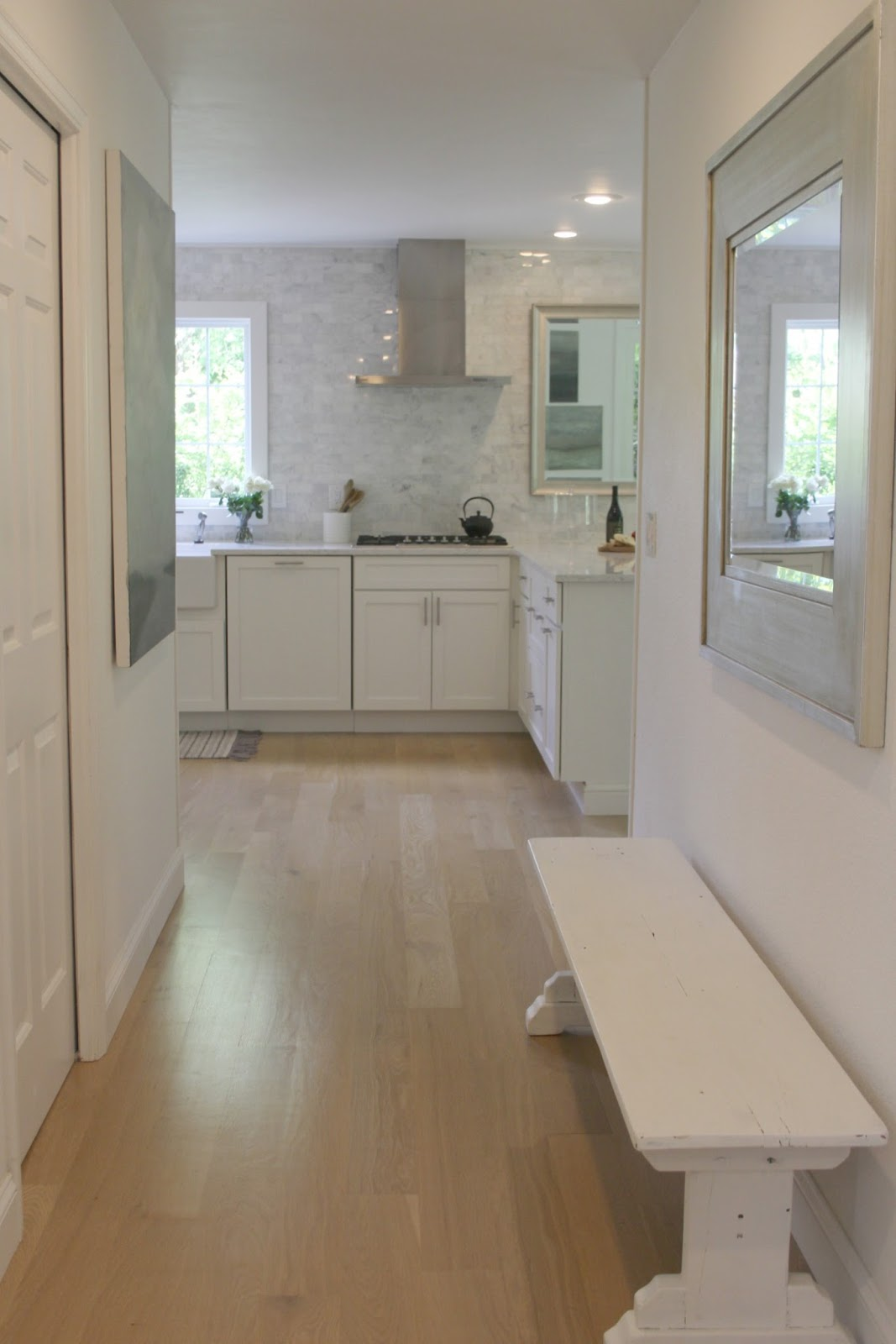 View of hallway adjacent to white modern farmhouse kitchen with white oak hardwood flooring and marble subway tile. Desgn by Hello Lovely Studio. #whitekitchen #whitedecor #kitchendecor #farmbench #shakercabinets #whitecabinets #serene #hellolovelystudio #modernfarmhouse #whitefarmhouse #farmhousekitchen