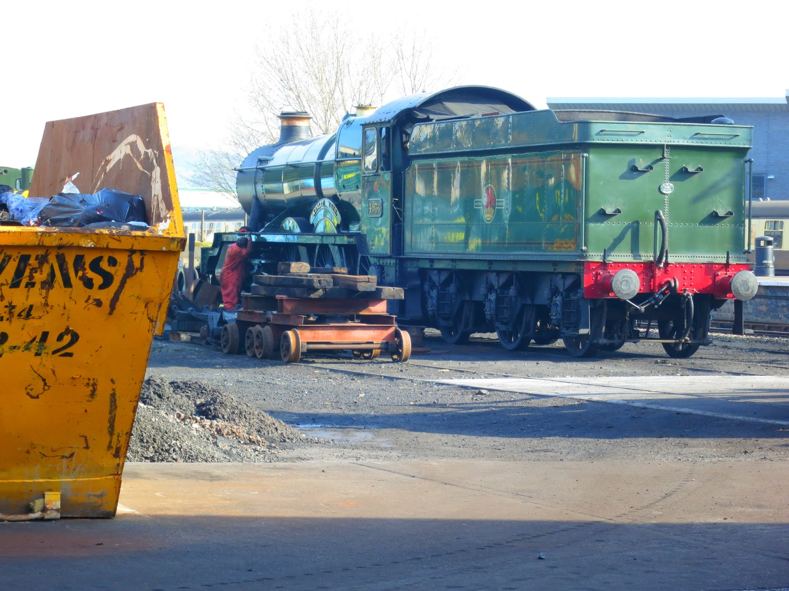 Green steam engine and yellow skip in yard. Minehead.
