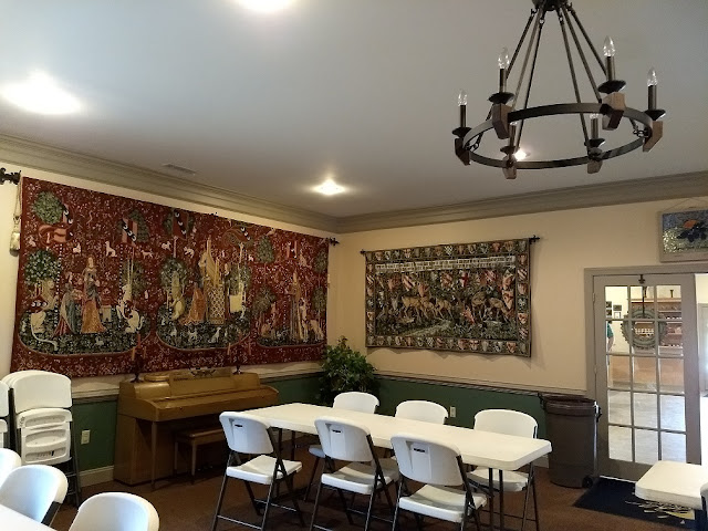 Wine testing room with two red ornate rugs on a walls and old piano. Several white rectangular tables and folding chairs.