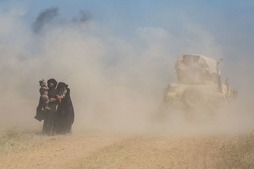 Powerful Heart-Breaking Pictures Of The Battle Of Mosul - A humvee passes civilians fleeing battles in Musharrifah