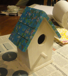 Wooden birdhouse with coat of gesso and blue decoupaged roof